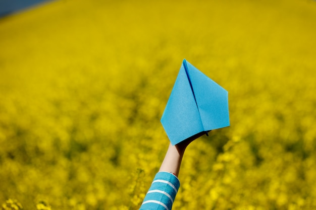 Paper airplane in children hands on yellow background.