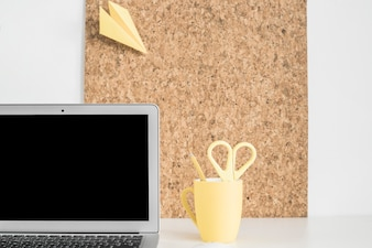 Paper airplane on cork board with laptop and cup holder