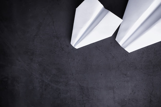Бумажный самолетик на столе. модель оригами на темном фоне. концепция. творческая трата времени.