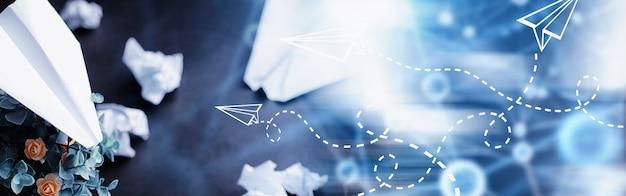 テーブルの上の紙飛行機。暗い背景の折り紙モデル。コンセプト。時間の創造的な無駄。