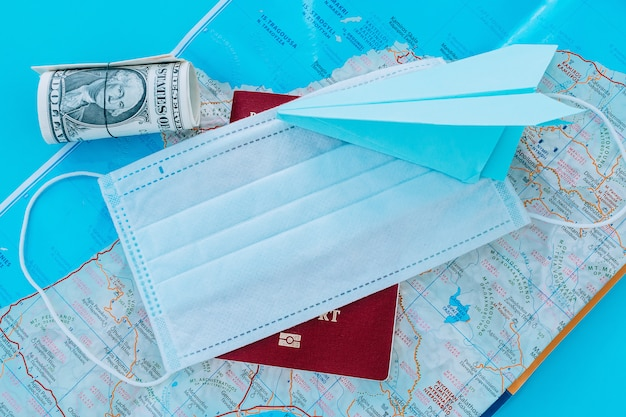 紙飛行機、防護マスク、ドル、パスポート。コロナウイルスのパンデミックによる飛行禁止の概念。