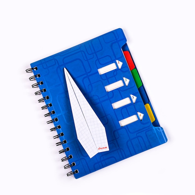 Paper airplane with the inscription dream on a blue notebook