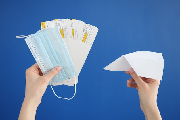 Paper airplane with tickets and protective medical mask in hands on blue wall