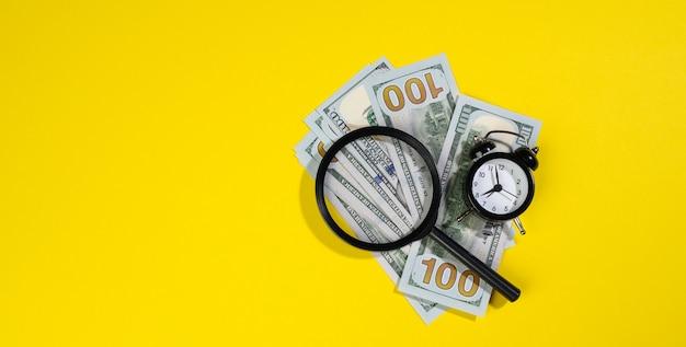 Бумажные американские стодолларовые банкноты и увеличительное стекло на желтой поверхности. концепция поиска заработка, прибыли с меньшими затратами времени, вознаграждения. банер, копировать пространство