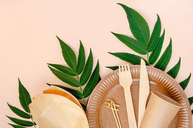 ピンクの背景に紙と竹の食器。ゼロウェイストコンセプト