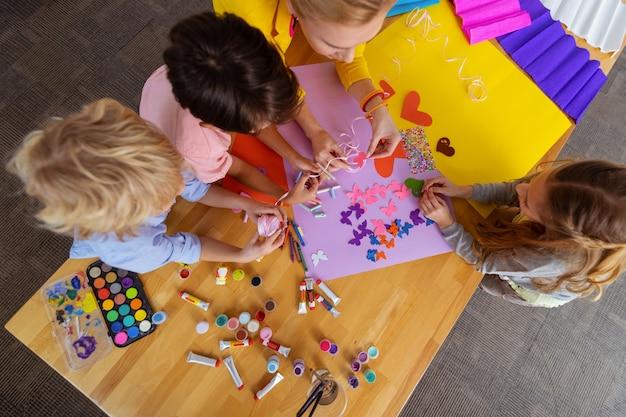 紙とガッシュ。レッスンでカラフルな紙とガッシュを使用してスマートなかわいい生徒と小学校の先生