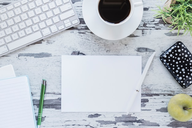 Бумага и карандаш возле клавиатуры и кофейной чашки
