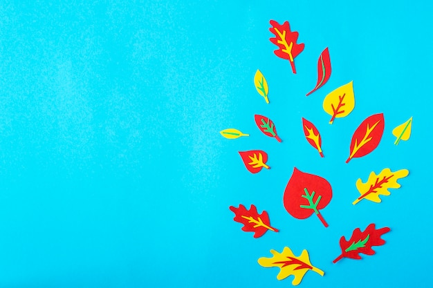 Paper applications of autumn leaves on a blue background
