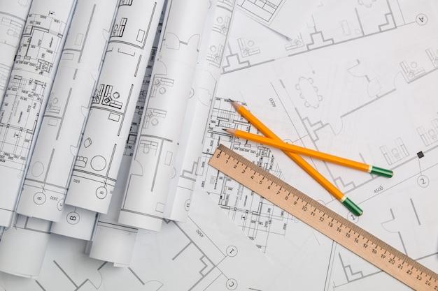 Бумажные архитектурные чертежи, чертежи, линейки и карандаши. инженерный проект