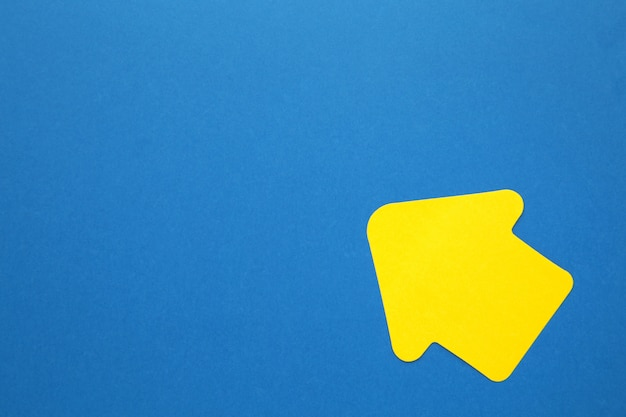 Paper arrow shapes on blue background for creative projects. top view