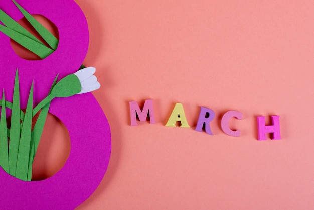 Paper art eight number cut of bright pink paper against the pnk background decorated with paper cut snowdrops. 8 march, international women's day background with empty space for text.