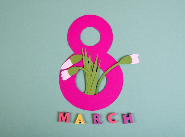 Paper art eight number cut of bright pink paper against the turquoise background decorated with paper cut snowdrops. 8 march, international women's day background with empty space for text.