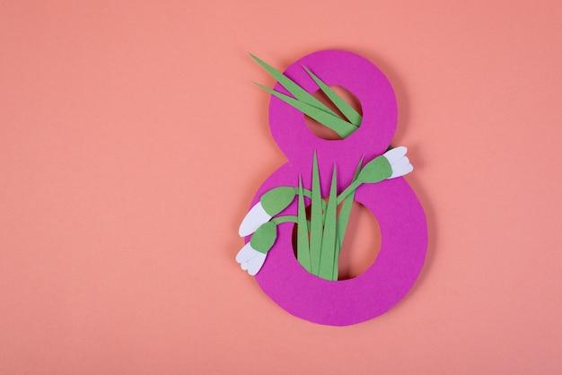 Бумажное искусство восьмизначная вырезка из ярко-розовой бумаги на фоне пнк, украшенная вырезанными из бумаги подснежниками. 8 марта, международный женский день фон с пустым пространством для текста.
