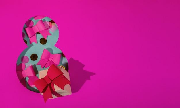 Бумажное искусство восьмизначный вырез из ярко-розовой бумаги на бирюзовом фоне, оформленный бантами из бумаги конфетти и одной подарочной коробкой.