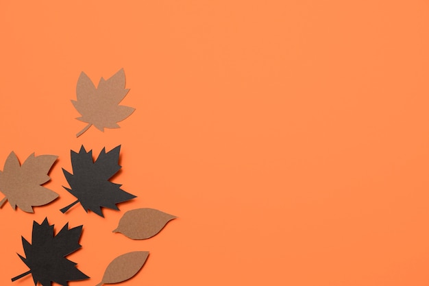 Paper autumn leaves on orange background with copy space