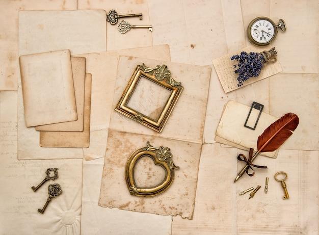 빈티지 액세서리, 편지, 황금 사진 프레임, 안경, 열쇠, 시계, 마른 라벤더 꽃이 있는 종이 배경