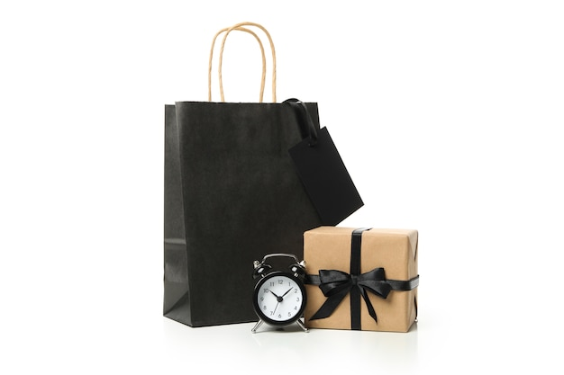 Paper bag, alarm clock and gift box isolated on white