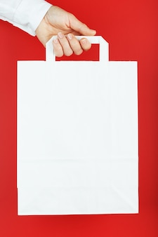 Paper bag at arm's length, white craft bag for takeaway isolated on red background. packaging template layout with space for copying, advertising.