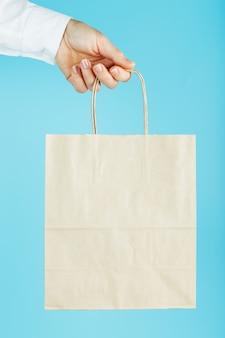 Бумажный мешок на расстоянии вытянутой руки, коричневая сумка ремесла для выноса, изолированная на синем фоне. упаковка шаблона макета с пространством для копирования, рекламы.