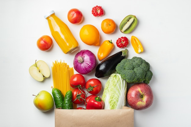 Paper bag of different health food on a table.