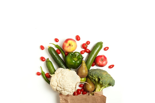 Paper bag of different healthy farm vegetables and fruits isolated on a white background. top view. flat lay with copy space.