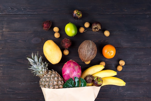 Paper bag of different healthy tropical fruits on dark wooden background. top view.
