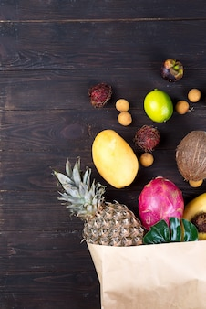 Paper bag of different healthy tropical fruits on dark wooden background.