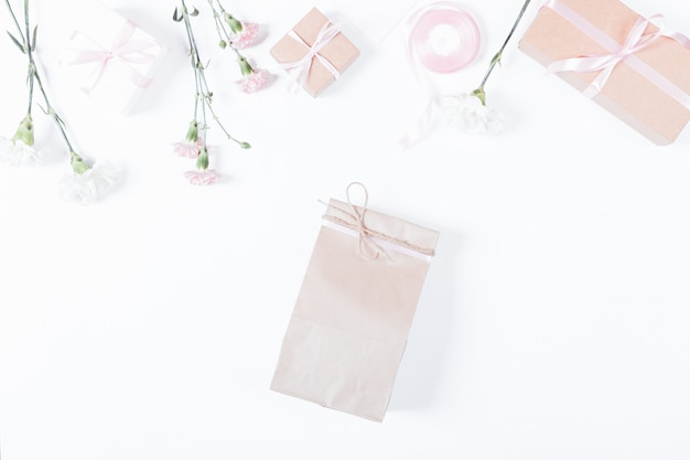 Paper bag, flowers, boxes with gifts and ribbons on white table, top view