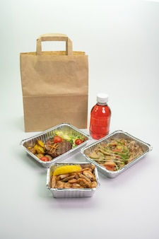 Paper bag foil containers and mors on an isolated background. contactless food delivery during the quarantine period