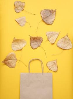 ショッピングのための紙袋、黄色のテーブルに落ちた紅葉。秋の買い物、販売、平面図、ミニマリズム