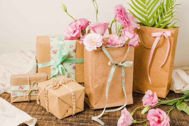 Paper bag full of fresh flowers and wrapped present gift over wooden surface
