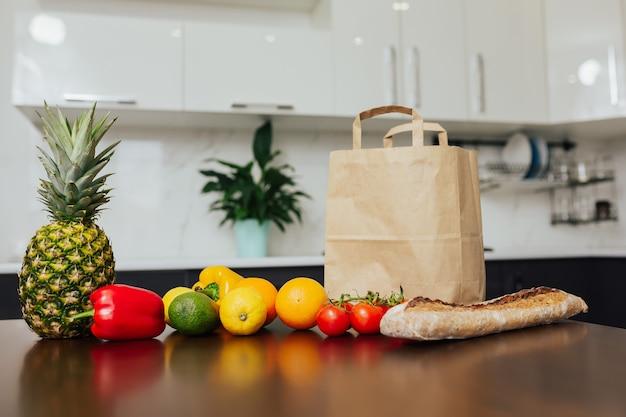 さまざまな野菜や果物の隣にある木製のキッチンテーブルに健康食品がいっぱい入った紙袋。