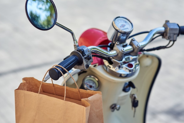 Paper bag hanging on scooter standing outdoors selective focus