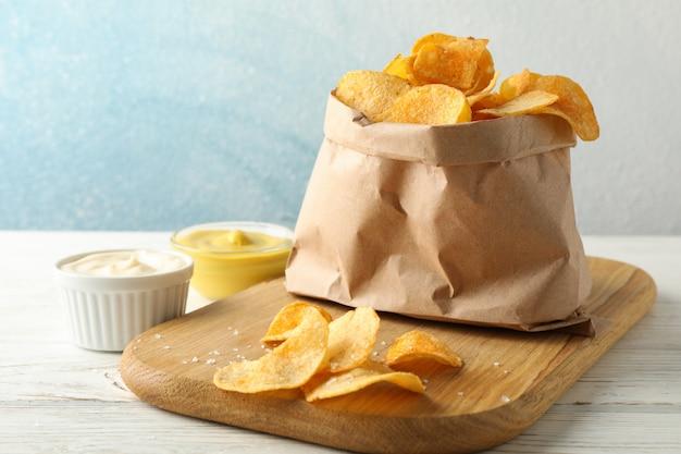 감자 칩의 종이 봉지. 맥주 간식, 커팅 보드에 소스, 흰색 나무, 텍스트를위한 공간