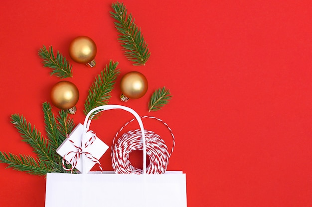 Бумажный пакет на красном фоне с подарочной коробкой шары новогодняя елка концепция подготовки рождественского подарка