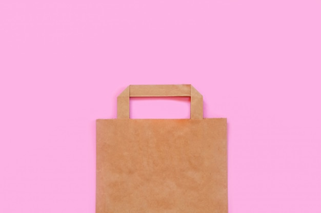 Paper bag on a pink background. recycling and plastic rejection