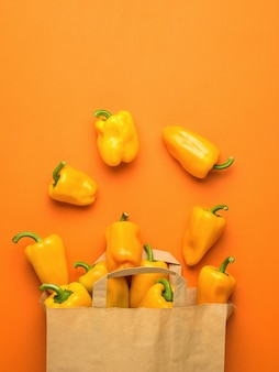 A paper bag and scattered bell peppers on an orange background. vegetarian food. flat lay.