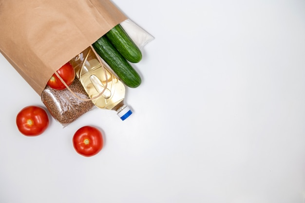 Paper bag set of raw cereals, grains, pasta and canned food on a white table. copy space, flat lay. crisis food stock for coronavirus quarantine isolation period. food delivery, donation