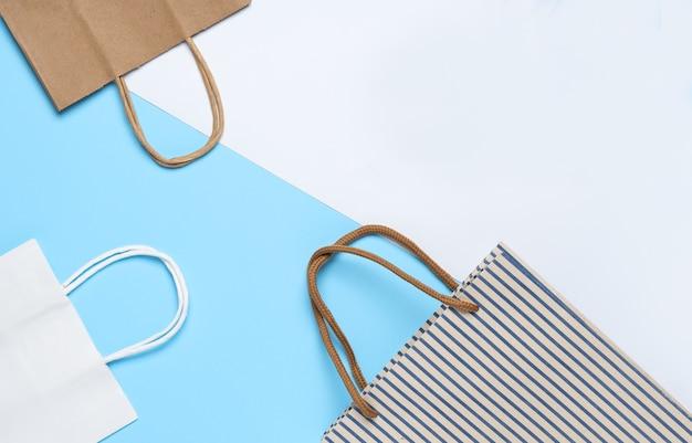 Бумажный пакет, сумка для покупок синего, белого и коричневого цвета на синем и белом фоне