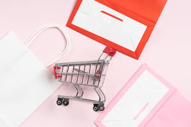 Бумажный пакет, хозяйственная сумка розового и белого цвета на розовом.