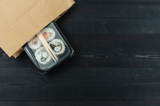 黒の木製の背景に紙袋寿司トレイ。スペースをコピーします。食品のコンセプト。