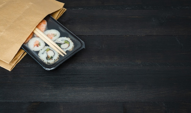 Поднос суши бумажного пакета на черном деревянном столе. концепция питания.