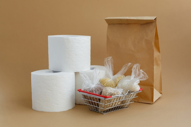 Paper bag toilet paper and various cereals in small plastic bags in grocery basket rice and oatmeal buckwheat and millet
