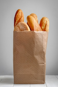 A paper bag with bread on the grey background.