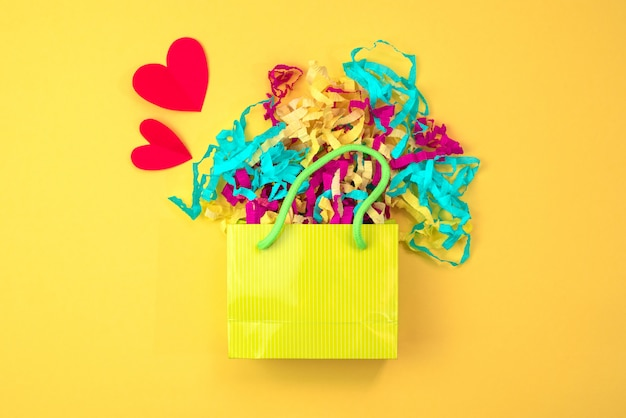 Paper bag with colored streamers on a bright yellow background