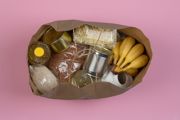 Paper bag with a crisis food supply for the period of quarantine isolation on a pink background