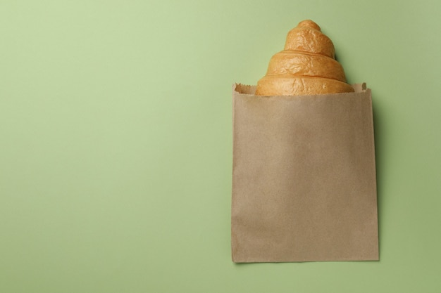 緑にクロワッサンが入った紙袋