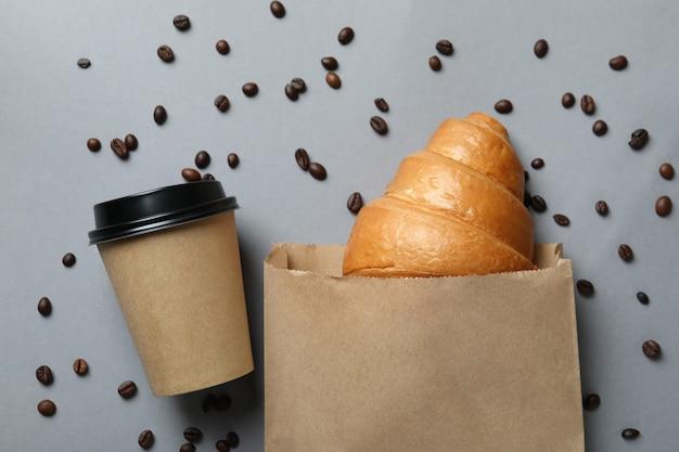 크루아상, 종이 컵 및 커피 씨앗이있는 종이 봉지