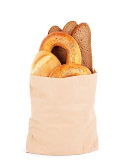 白い背景の上の異なる種類のパンと紙袋