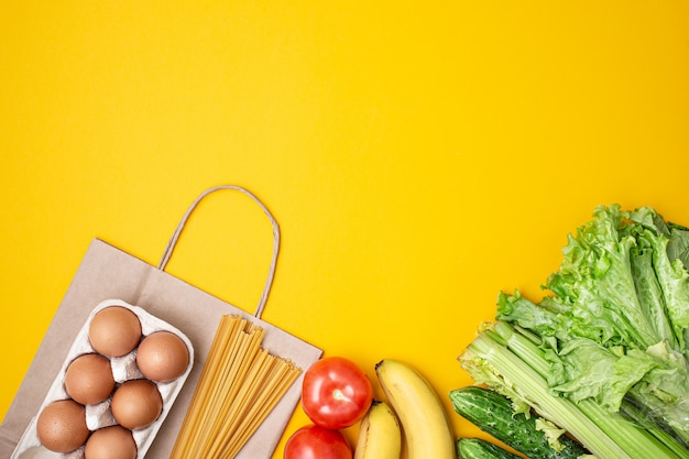 Paper bag with food, canned food, tomatoes, cucumbers and bananas on a yellow background.